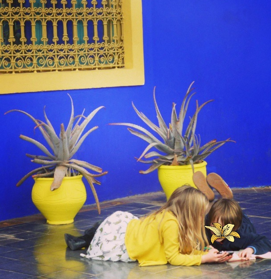children colouring in against a beautiful blue wall in Yves St Laurent's garden, Morocco